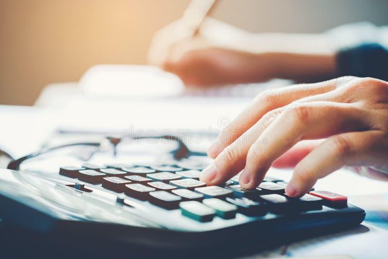 Les mains du ` s d'homme d'affaires avec la calculatrice au bureau et aux données financières ont coûté économique image libre de droits