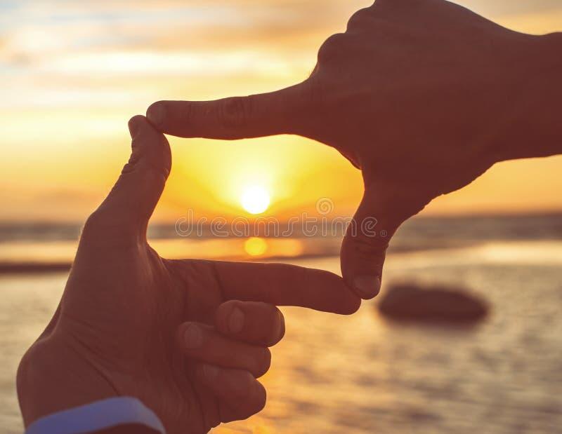 Les mains du ` s d'homme de cadre de doigt de composition capturent le coucher du soleil images libres de droits