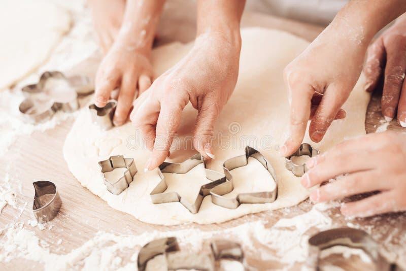 Les mains du ` s de femelle et d'enfants font la forme pour des biscuits avec l'aide des moules de cuisson image libre de droits