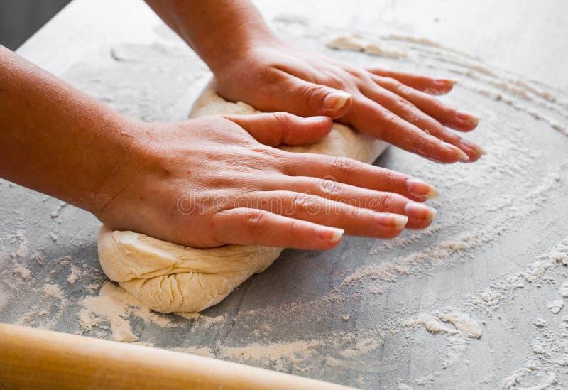 Les mains du ` s de femme malaxent la pâte sur la table en bois image libre de droits