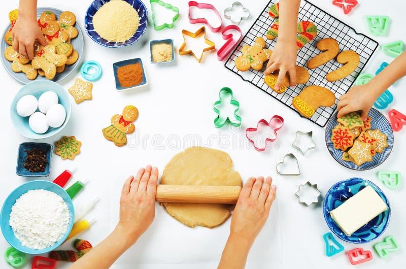 Les mains du ` s de femme roulent la pâte de gingembre avec des mains d'enfants, roucoulement de pain d'épice photo libre de droits