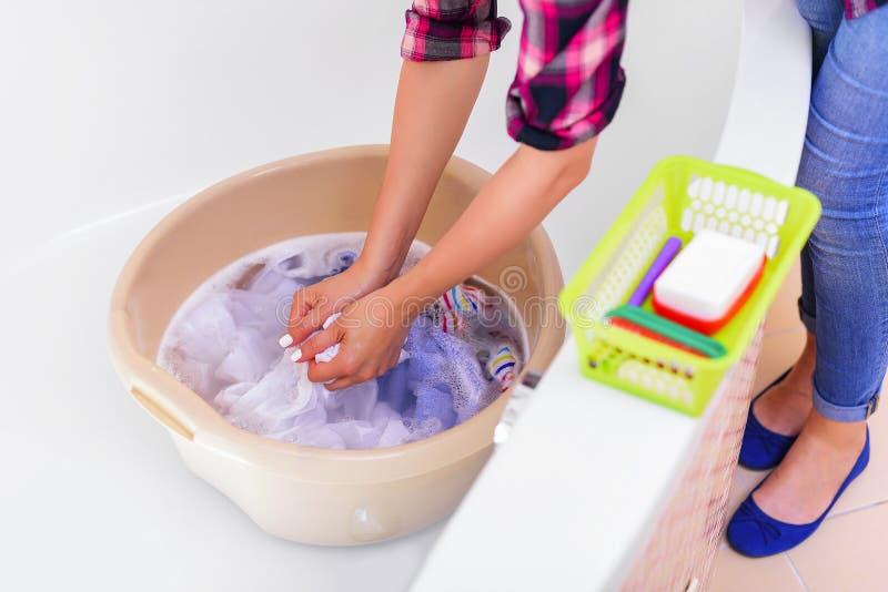 Les mains du ` s de femmes lavent des vêtements dans le bassin photographie stock libre de droits