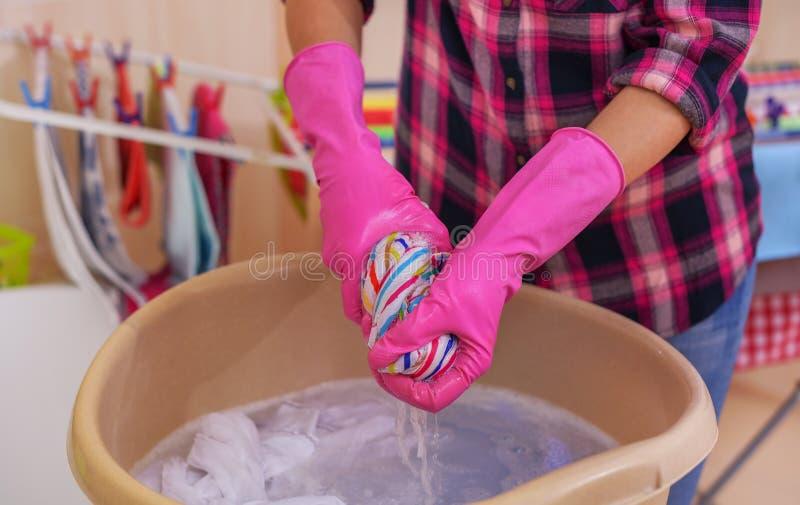 Les mains du ` s de femmes lavent des vêtements dans le bassin image libre de droits