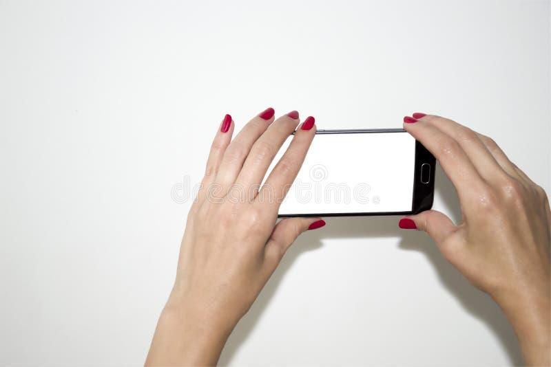 Les mains du ` s de femmes tiennent le téléphone photo libre de droits