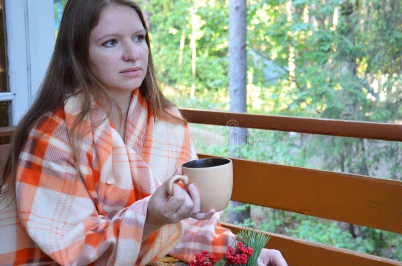 Les mains du ` s de femmes tiennent une tasse de boisson chaude, d'automne, de feuilles de chute, de tasse de café de cuisson à l photo libre de droits