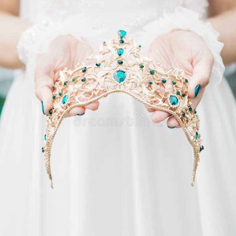 Les mains du ` s de jeune mariée tiennent la belle couronne avec les gemmes vertes image stock