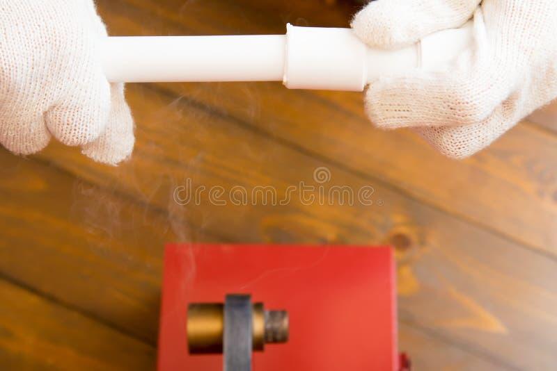 Les mains du travailleur fixent le raccord et le tuyau dans le processus de réchauffement, sur un fond en bois image libre de droits