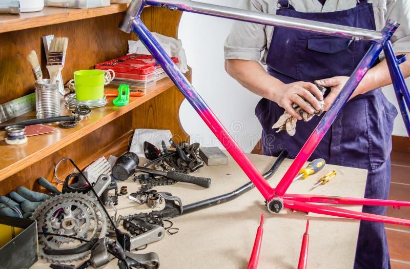 Les mains du vrai cadre de nettoyage de mécanicien de bicyclette font du vélo photographie stock