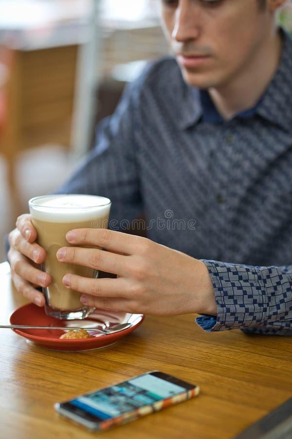 Les mains en gros plan de l'homme avec le grands latte et smartphone photo stock