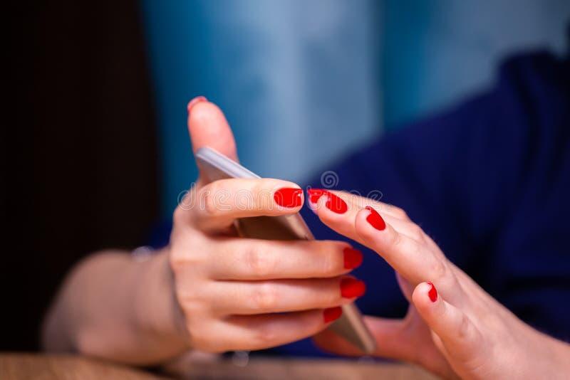 Les mains en gros plan et femelles avec la manucure rouge utilisent un smartphone sur un fond blanc profondeur de zone limit?e photographie stock libre de droits