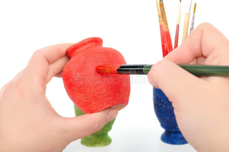 Les mains et le balai femelles peignent un vase image libre de droits