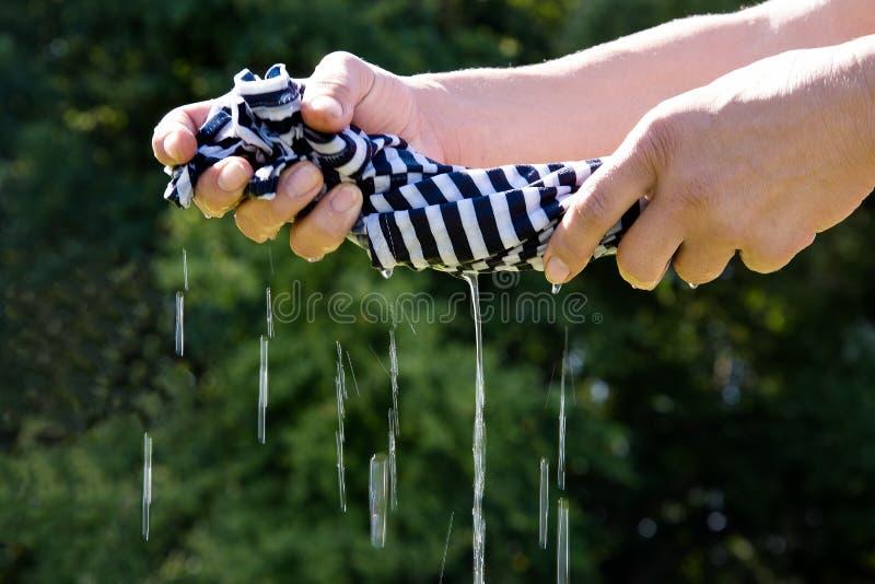 Les mains extorquent le tissu image stock