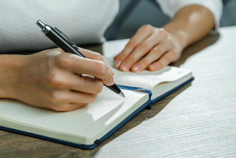 Les mains femelles écrivent dans un carnet image stock