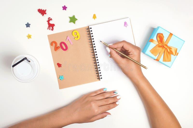 Les mains femelles écrivent sur le carnet Nouvelle année 2019 buts concept de planification de Noël Boîte-cadeau, décorations, ca photographie stock