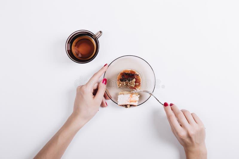 Les mains femelles avec la manucure rouge ont coupé un morceau de gâteau avec les FO image libre de droits