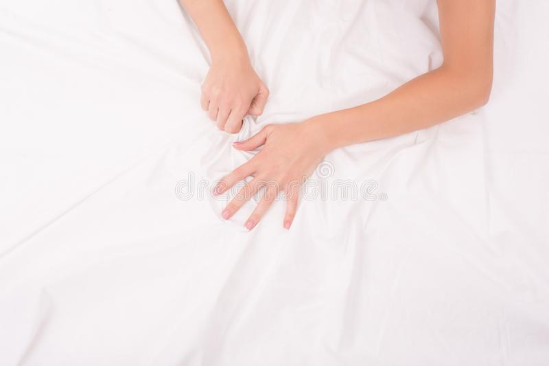 Les mains femelles chiffonnent dessus la feuille blanche, couple ayant le sexe, foyer sur des mains image stock