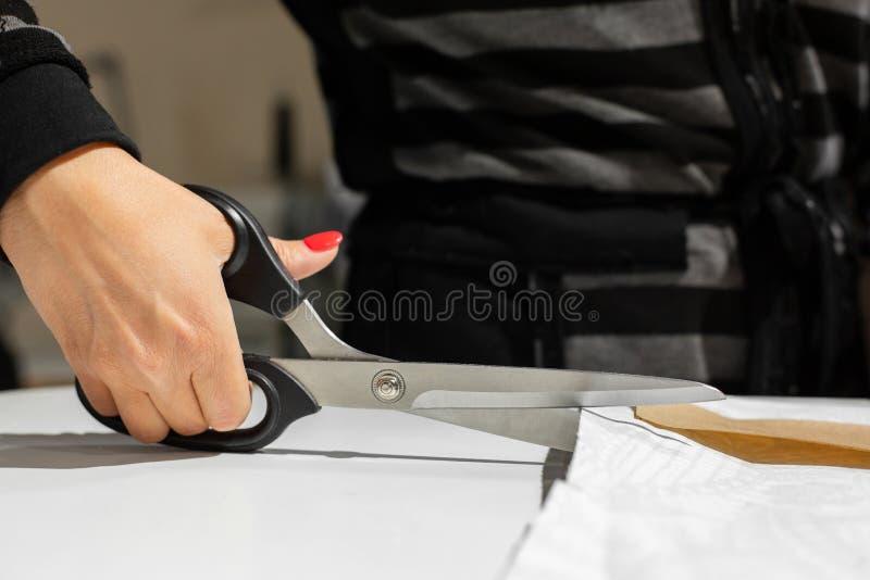 Les mains femelles coupent le tissu avec des ciseaux de tailleurs sur le modèle du papier image stock