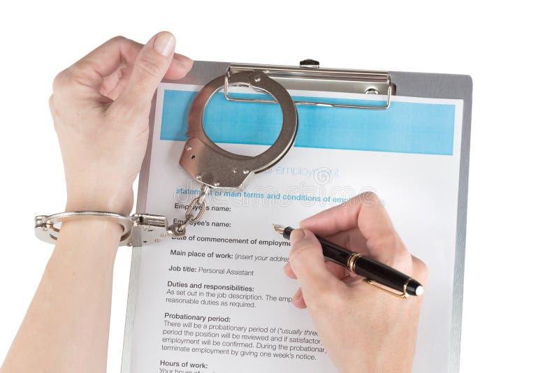 Les mains femelles dans des menottes signe le contrat de travail photographie stock libre de droits