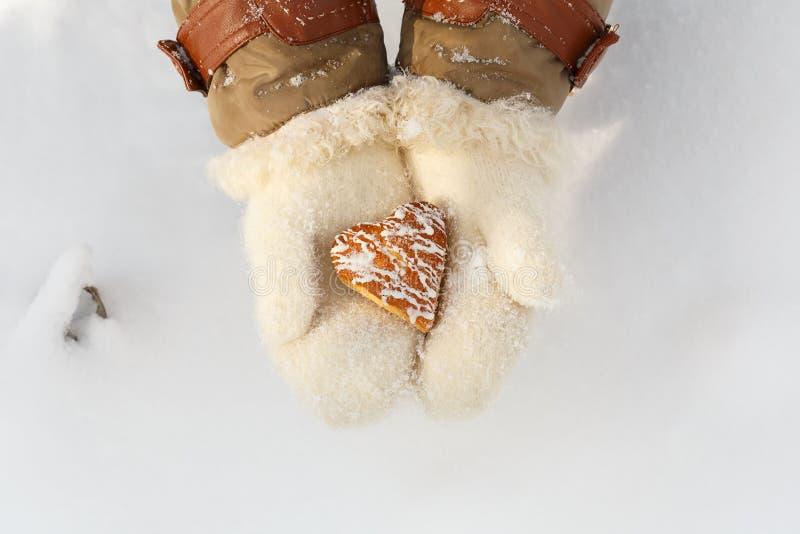 Les mains femelles dans des mitaines blanches de laine tiennent la belle forme de coeur photographie stock
