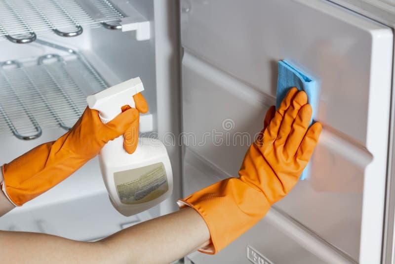 Les mains femelles dans les gants protecteurs essuient le réfrigérateur à l'intérieur images stock