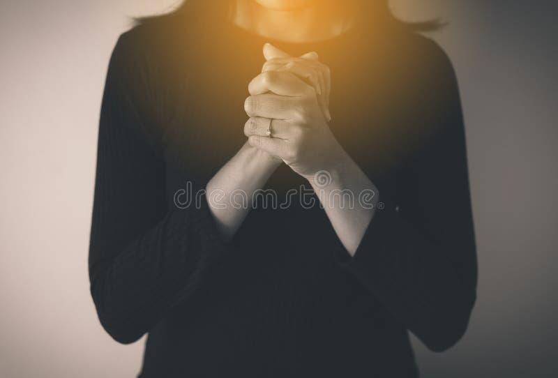 Les mains femelles de prière ont étreint ensemble, femme avec la main en position de prière, noir et blanc modifié la tonalité photographie stock