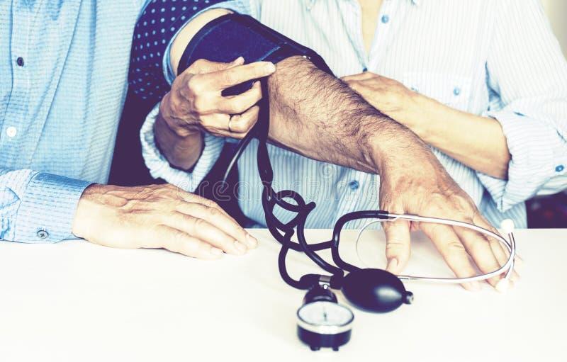 Les mains femelles de th?rapeute avec une tension art?rielle de mesure de tonometer classique d'un homme dans la chambre ? la mai photo stock