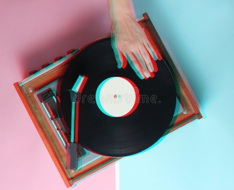 Les mains femelles emploient le rétro joueur de vinyle sur un fond en pastel rose bleu Effet de problème Le DJ Vue supérieure image stock