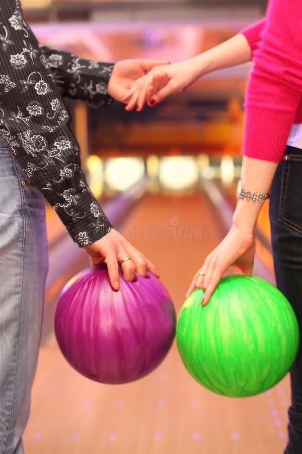 Les mains femelles et mâles avec des billes dans le bowling matraquent images libres de droits