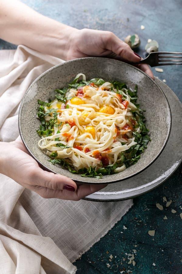 Les mains femelles gracieuses tiennent un plat des spaghetti avec des oeufs et des herbes de caille Cuisine m?diterran?enne tradi photos libres de droits
