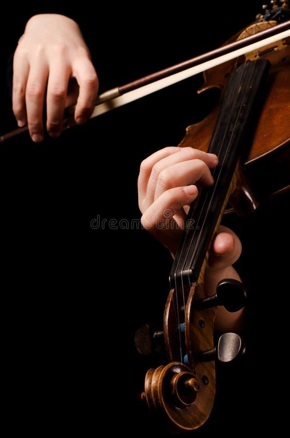 Les mains femelles jouent un violon image libre de droits