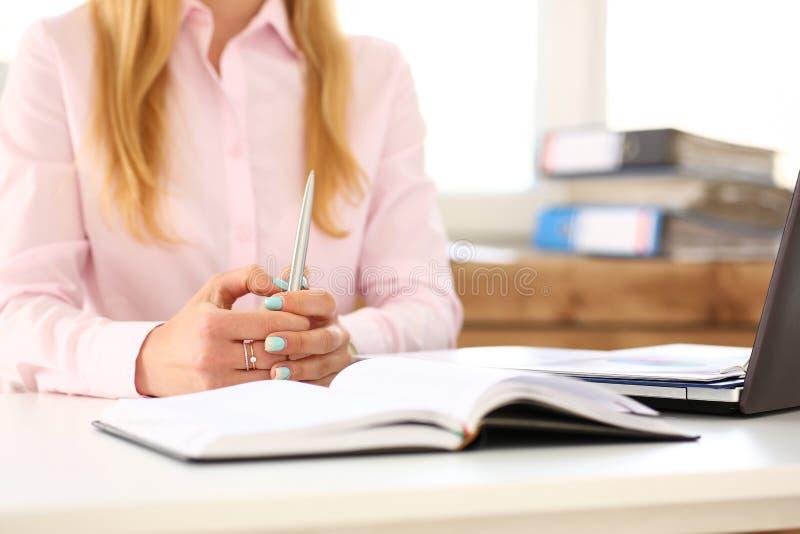 Les mains femelles ont croisé sur la table avec le stylo argenté photo libre de droits