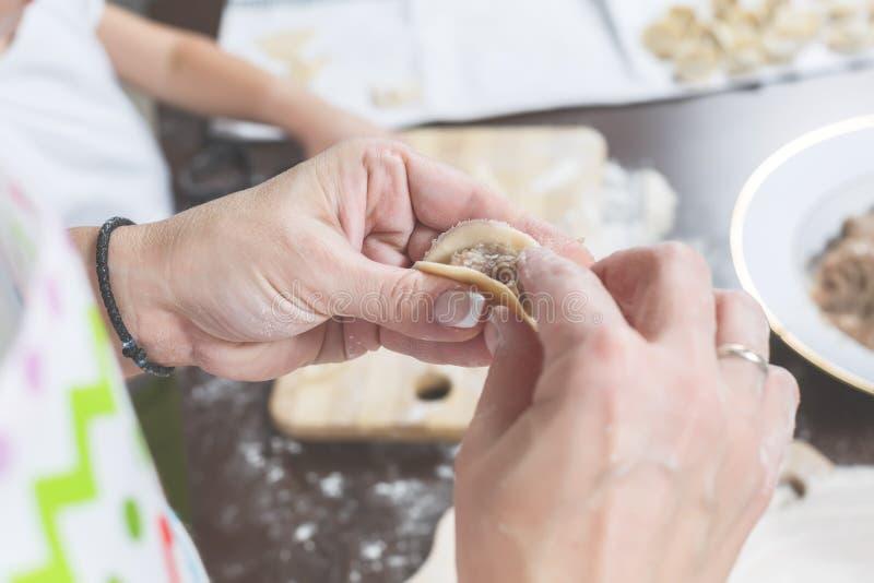 Les mains femelles ont mis le remplissage de la viande hachée sur un morceau de pâte photos stock