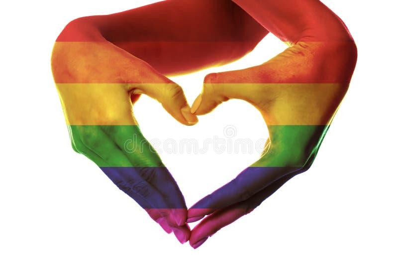 Les mains femelles ont peint comme drapeau d'arc-en-ciel faisant le coeur sur le fond blanc Concept de LGBT photos stock