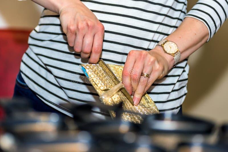 Les mains femelles ouvrent impatiemment le cadeau bien emballé de Noël avec le couteau photos stock