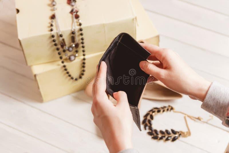Les mains femelles ouvrent la bourse vide contre des femmes habillement et accessoires après l'achat photo stock