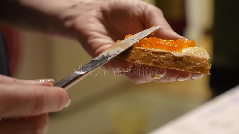 Les mains femelles répand le caviar rouge avec le couteau sur le pain avec du beurre pour des casse-croûte de partie image libre de droits