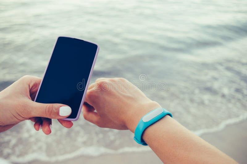 Les mains femelles reçoivent des données du bracelet intelligent à un téléphone portable photographie stock