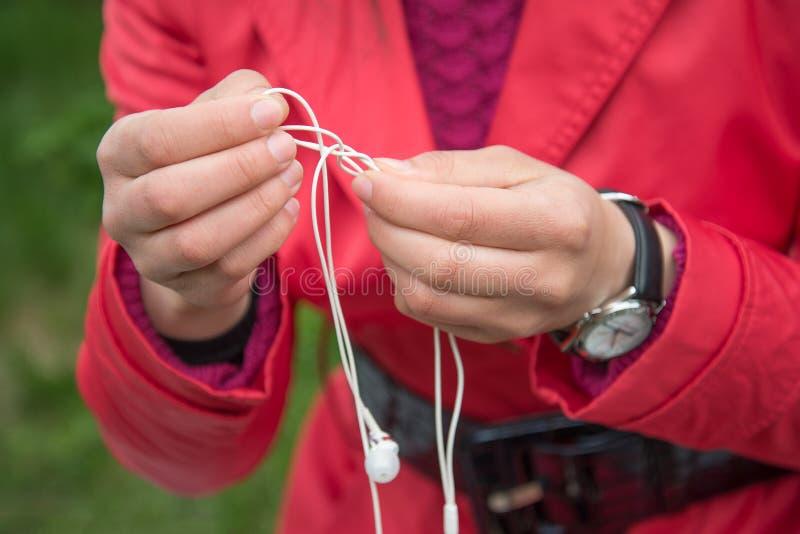 Les mains femelles se démêlent les petits écouteurs blancs extérieurs photos libres de droits