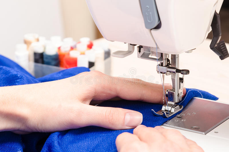 Les mains femelles sont occupées par la couture image stock