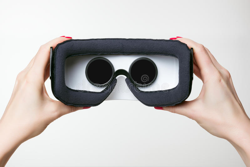Les mains femelles tenant la réalité virtuelle google, le fond blanc photos stock