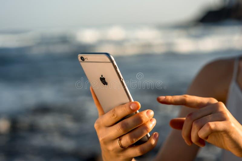 Les mains femelles tenant le nouvel iPhone 6s espacent le gris photo stock