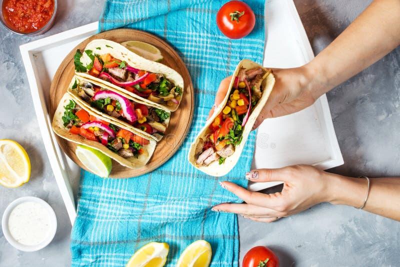 Les mains femelles tiennent les tacos mexicains de porc avec des légumes Pasteur d'Al de Tacos sur le fond rustique bleu en bois  photo libre de droits