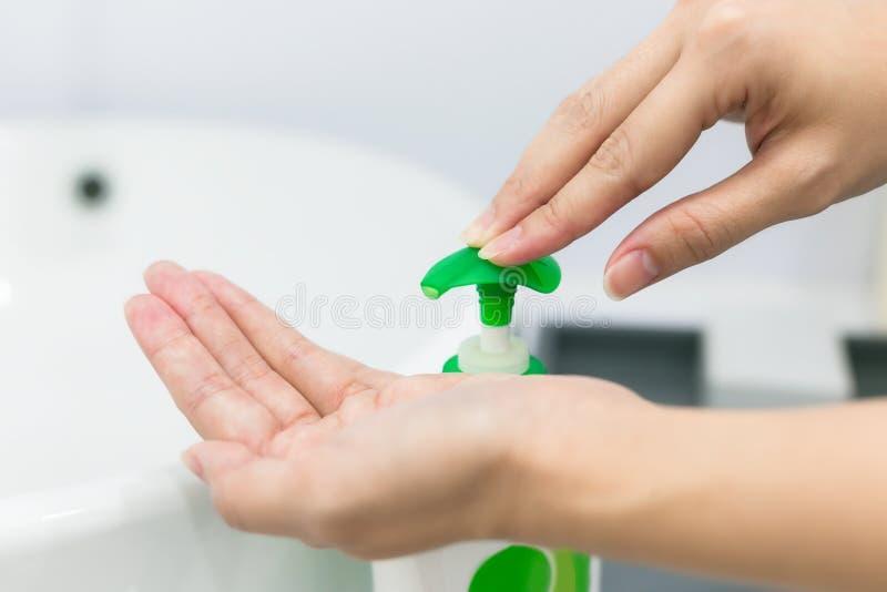 Les mains femelles utilisant le lavage remettent le distributeur de pompe de gel d'aseptisant photos stock