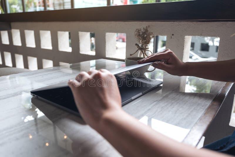 Les mains ferment et ouvrent un ordinateur portable sur la table après de finition utilisant lui photo stock