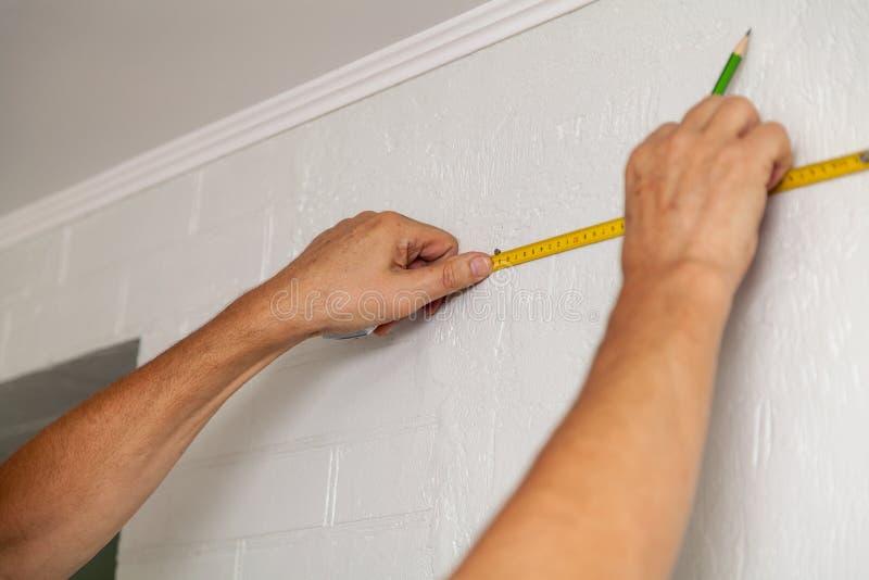 Les mains font l'inscription de mur avec le ruban métrique et le crayon photos stock