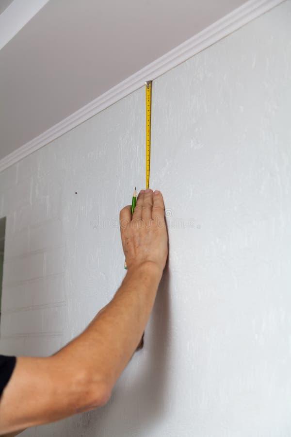 Les mains font l'inscription de mur avec le ruban métrique et le crayon images libres de droits