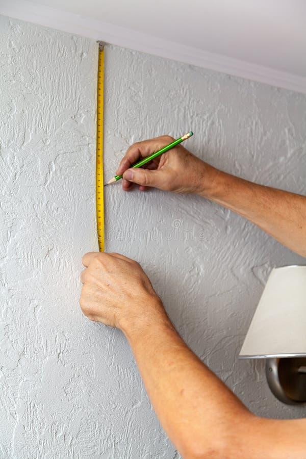 Les mains font l'inscription de mur avec le ruban métrique et le crayon photographie stock