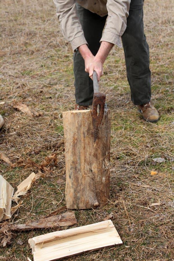 Les mains de l'homme avec du bois de division de hache photo stock