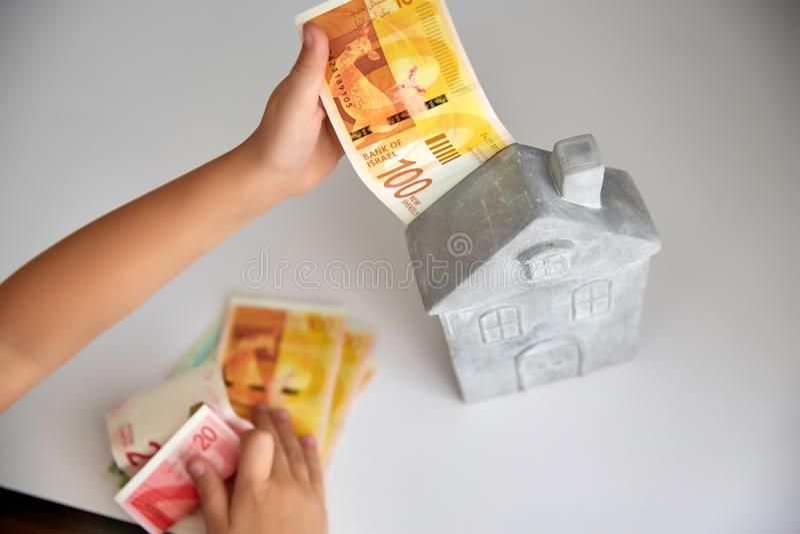 Les mains gardent l'Israélien de shekel de billets de banque sur un fond de construction photos stock