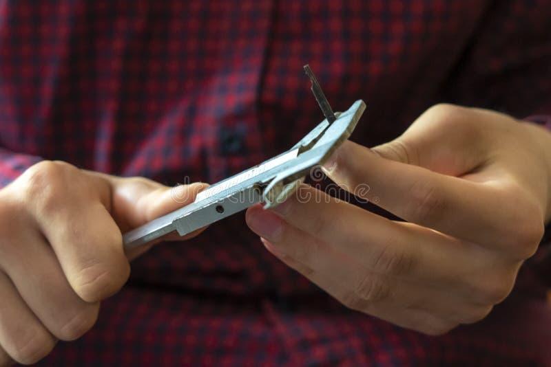 Les mains hautes étroites d'homme tiennent le calibre et mesurent les morceaux f en métal photo libre de droits